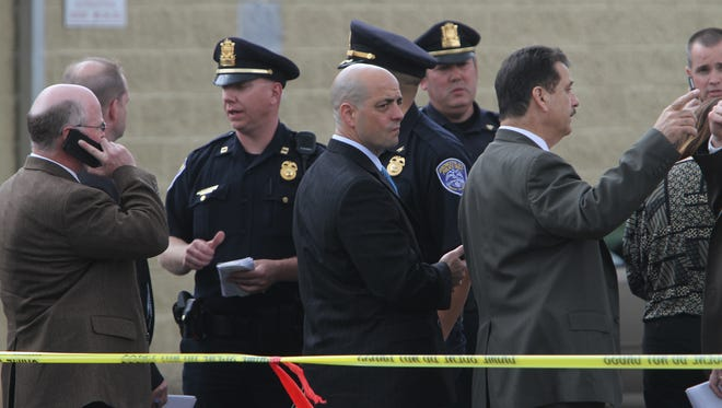 Lt. Frank Umbrino, center, and others confer about shooting.