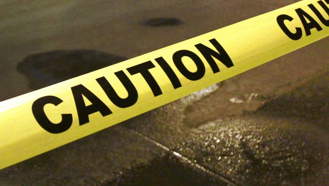 Caution tape warns passers-by of hazardous conditions.