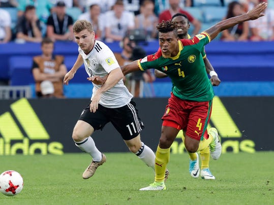 Germany's Timo Werner, left, and Cameroon's Adolphe Teikeu go for the ball during the Confederations Cup, Group B soccer match between Germany and Cameroon, at the Fisht Stadium in Sochi, Russia, Sunday, June 25, 2017. (AP Photo/Thanassis Stavrakis)