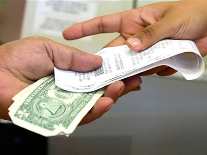 FILE - In this Friday, Nov. 23, 2012 file photo, a cashier hands a customer his change and receipt during a transaction at a Sears store, in Henderson, Nev. U.S. consumer spending fell in July, with a drop in auto purchases accounting for most of the weakness. Income growth also slowed in July. The Commerce Department says consumer spending edged down 0.1 percent last month after a 0.4 percent increase in June. It was the first decline in spending since January.
