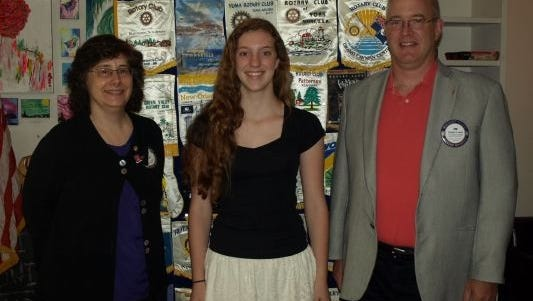 Red Hook Rotary President Chris Chale, left, poses with Abby Romm and Youth Exchange Officer Tim Lynch.