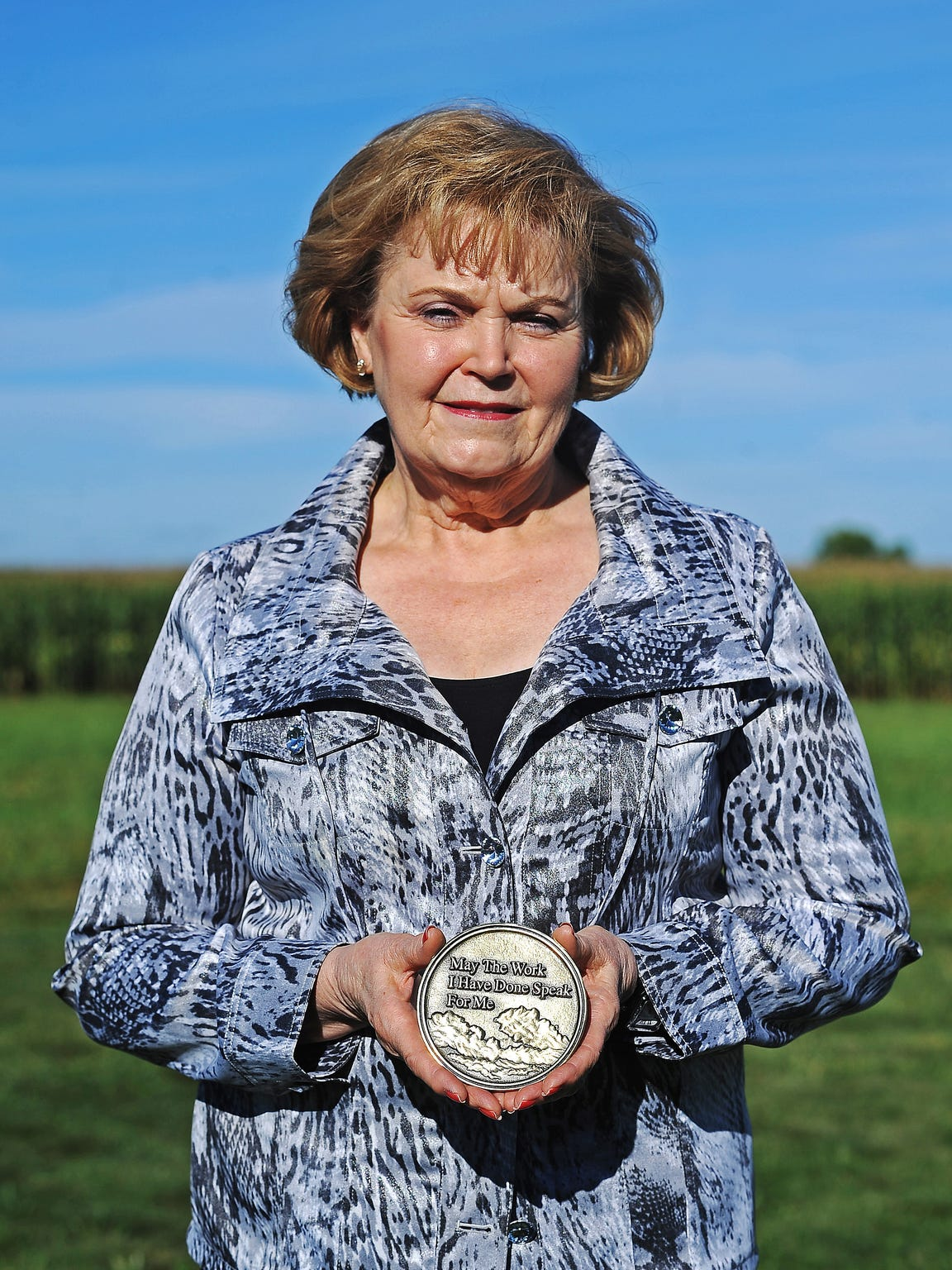 Karen Kratochvil poses for a portrait with a medallion from the funeral of her daughter, Tami Mielke. Kratochvil remembers a time when her daughter went inside after fireworks were shot off in the backyard. It was a result of her PTSD, Kratochvil said.