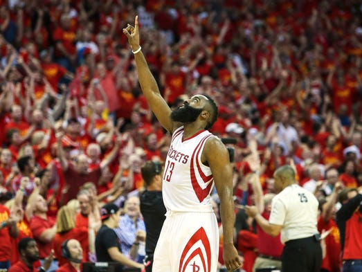 Houston Rockets guard James Harden (13) points up after