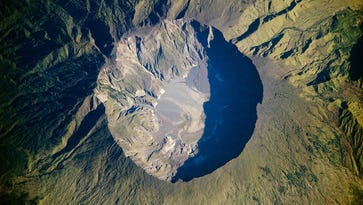 """Sulphuric gases rise from the crater of Mt. Tambora on the island of Sumbawa, Indonesia.  The eruption of Tambora in 1815 was the largest volcanic eruption in human history and resulted in a period of global cooling known as """"the year without a summer."""""""