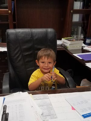 Kane Scott, the youngest child of Greg and Jaclyn, sits in his dad's chair in the Milan High School principal's office.