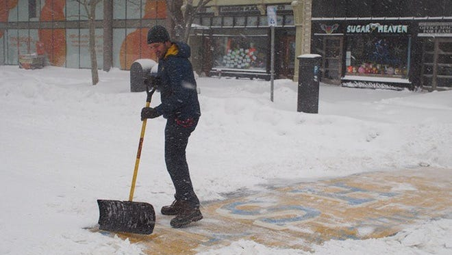 """Adam Reynolds was walking down the street taking pictures when he saw a """"mystery"""" man shoveling the finish line."""
