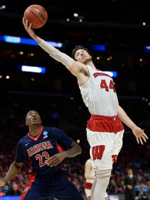 Wisconsin Badgers forward Frank Kaminsky (44) grabs a rebound against Arizona Wildcats forward Rondae Hollis-Jefferson (23) during the second half in the finals of the west regional of the 2015 NCAA Tournament at Staples Center in Los Angeles on March 28, 2015.