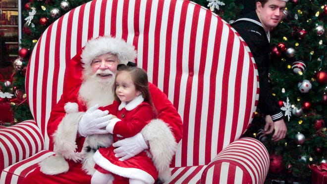 Tyler Walters pops up from behind Santa's chair to surprise daughter, Ava Walters, who is sharing her Christmas wish to have her Daddy home.