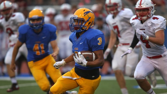 Carmel's #3 Jalen Walker moves the ball in first half action during the Center Grove at Carmel High School football game, Friday, September 4, 2015.