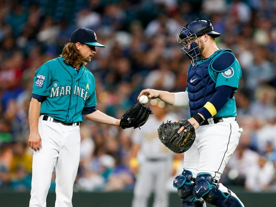 Mariners starter Mike Leake, left, receives a ball