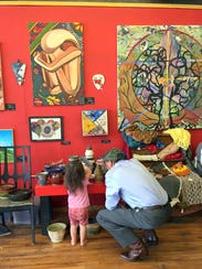 U.S. Sen. Tom Udall converses with a young artist while