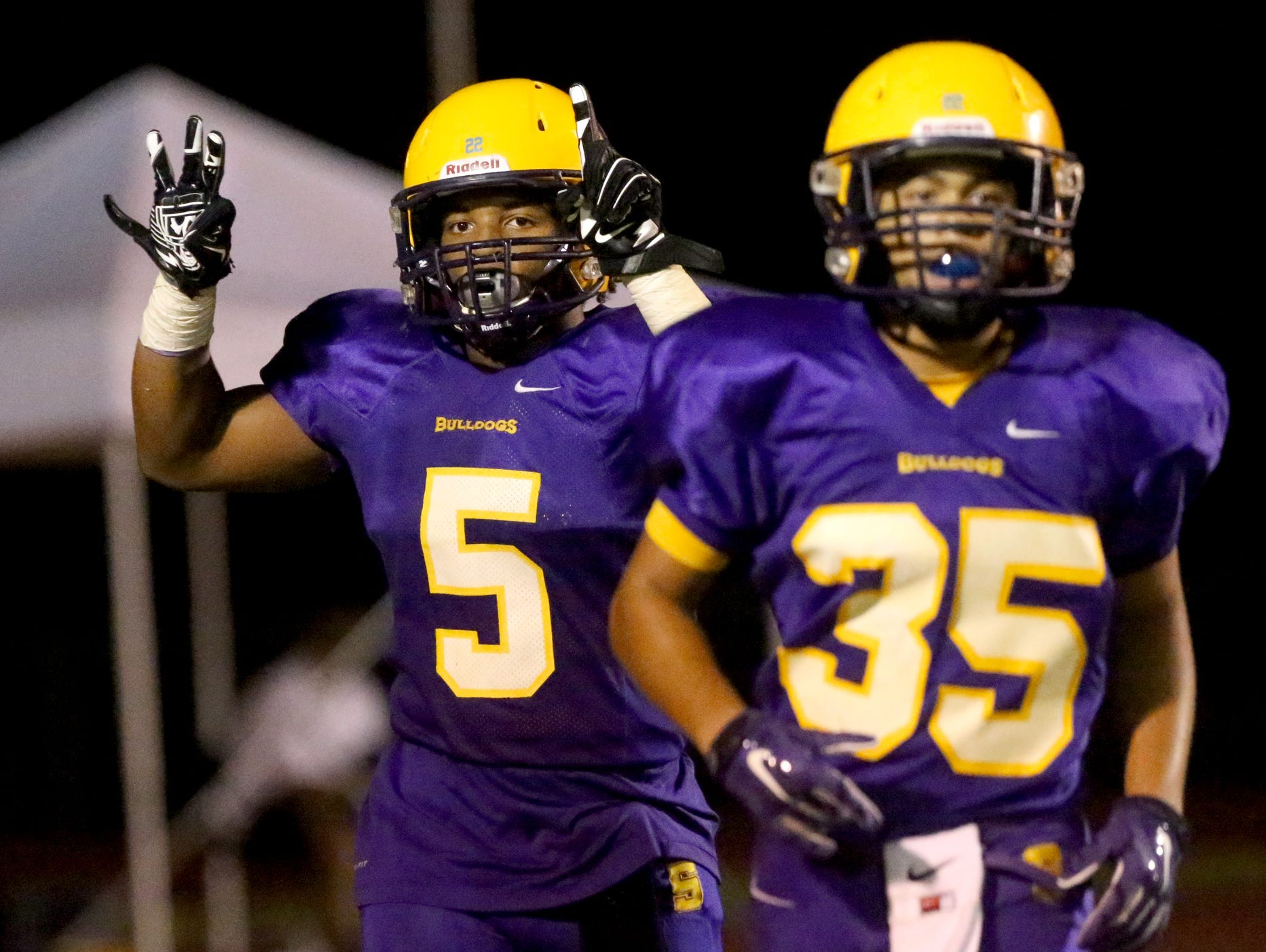 After scoring Smyrna's fourth touchdown against Siegel, Smyrna's Casey Perkins (5) holds up a 31 for injured teammate Deven Sims (31), who was taken to the hospital by ambulance earlier in the game against Siegel at Smyrna, on Friday Sept. 25, 2015. Smyrna teamate Blake Watkins (35) comes off the field with Perkins.