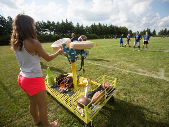 Sophomore manager Ashley Groshek feeds the football into a passing machine during Amherst football practice, Wednesday, Aug. 3, 2016.