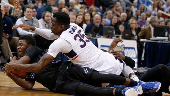 Former Tulsa forward Keondre Dew (left) and UConn center Amida Brimah battle for the ball in a college basketball game last season.