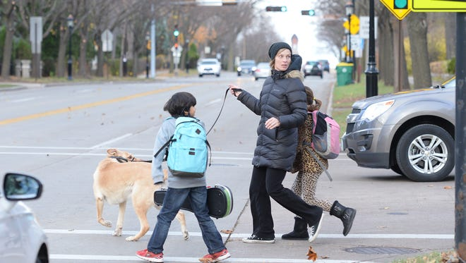 Crossing Monroe Avenue outside Aldo Leopold Community School has become an issue for parents and school officials. A parent walks with her two children and dog across the busy crosswalk.