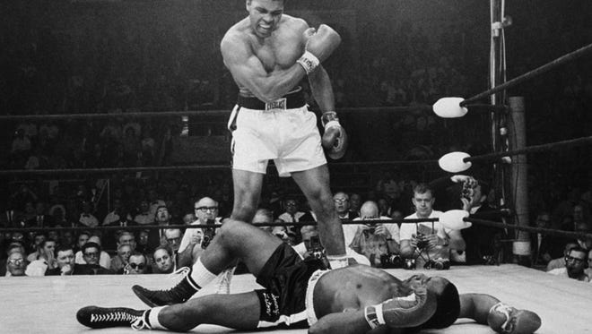 In this May 25, 1965, file photo, heavyweight champion Muhammad Ali stands over fallen challenger Sonny Liston, shouting and gesturing shortly after dropping Liston with a short hard right to the jaw in Lewiston, Maine.  Ali, the magnificent heavyweight champion whose fast fists and irrepressible personality transcended sports and captivated the world, died Friday at 74.