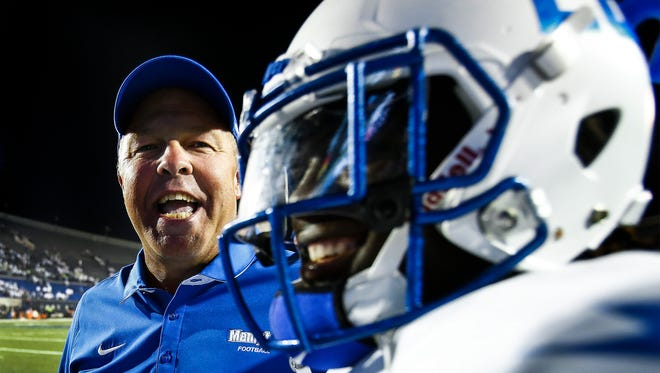 University of Memphis running backs coach Darrell Dickey (left) celebrates with running back Doroland Dorceus (right) after a 34-27 victory over Temple at Liberty Bowl Memorial Stadium. Dorceus, had a 71 yard touchdown run during third quarter action.