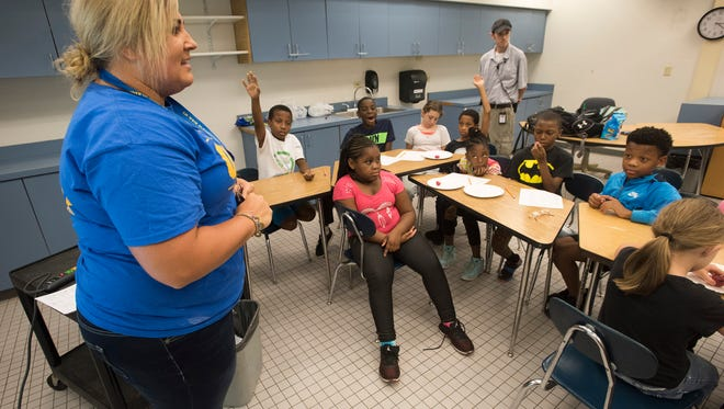 Erica Hankins, left, teaches a group of students attending a summer school program at C.A. Weis Elementary School how to classify fruits and vegetables during an in-class exercise Wednesday July 12, 2017.