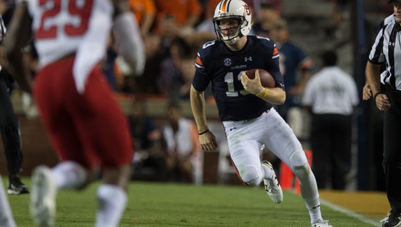 Auburn quarterback Sean White (13) runs downfield during