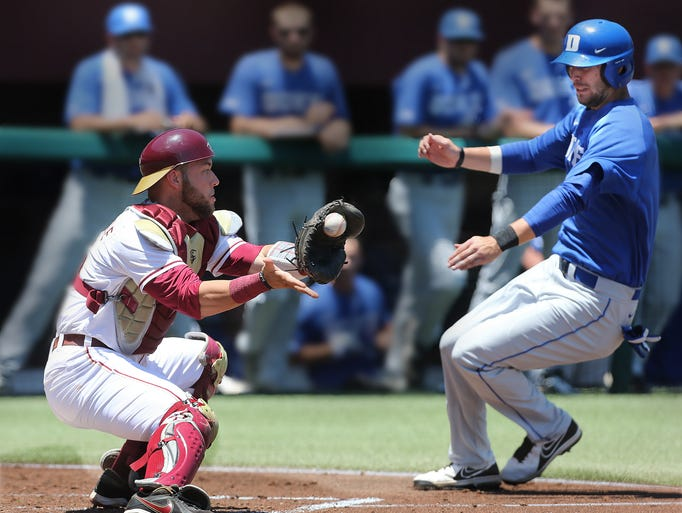 Catcher Danny De La Calle eyes a throw to nail Duke runner Ryan Deitrich at home. FSU honored their 7 senior players before the game and battled the Duke Bluedevils but fell two runs short during a Saturday 7-5 loss at Howser Stadium.