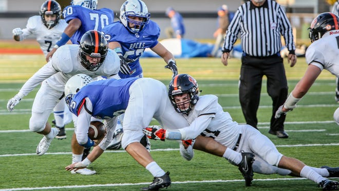 Brighton's Kyle Hook tackles Salem quarterback Ryan Young whlie Jack Johnson moves in.