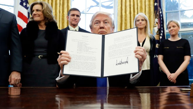 """President Donald Trump holds up a signed Presidential Memorandum in the Oval Office on Saturday. The document directs his administration to """"develop a comprehensive plan to defeat ISIS."""""""