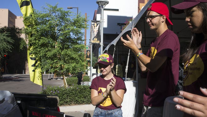 Student volunteers cheer as residents move into the Taylor Place dorms, 120 E Taylor Street, Phoenix.