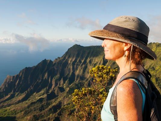 Mature woman in beautiful landscape at Kalalau Lookout, Kauai