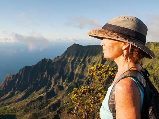 Mature woman in beautiful landscape at Kalalau Lookout, Kauai