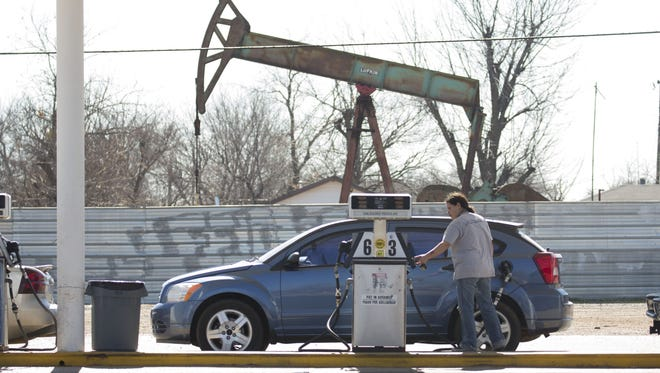 A motorist fills their car with gas at a gas station near an oil field pumping rig in Oklahoma City.