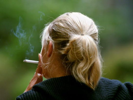 In this 2006 photo, a woman smokes during a break from work in Chicago.