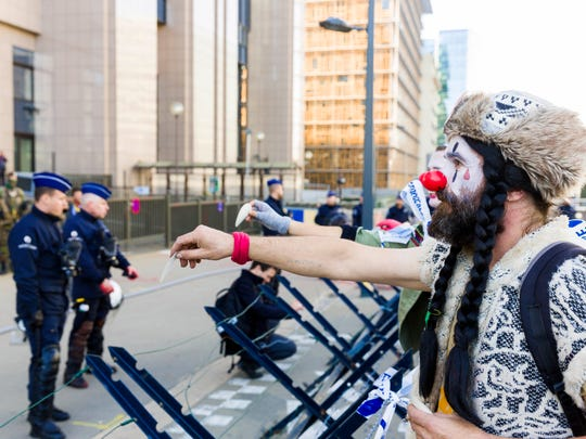 A demonstrator dressed as a clown attempts to hand