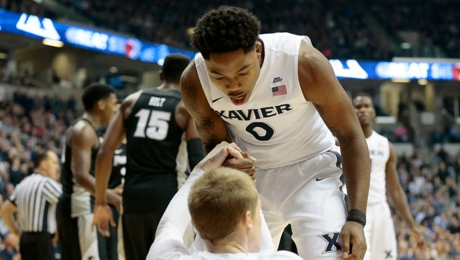 Xavier Musketeers forward Tyrique Jones (0) pulls up guard J.P. Macura (55) after he draws a foul under the basket in the first half of the Big East Conference game between the Xavier Musketeers and the Providence Friars at XU's Cintas Center.