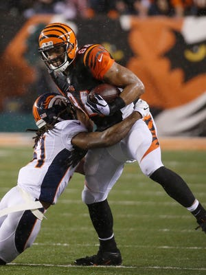 Cincinnati Bengals tight end Jermaine Gresham (84) is tackled by the Denver Broncos strong safety Omar Bolden (31) in the fourth quarter at Paul Brown Stadium.