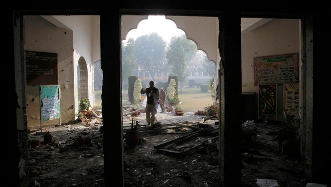 In this Dec. 17, 2014 file photo, a Pakistan army soldier inspects the Army Public School that was attacked by Taliban gunmen, in Peshawar, Pakistan.