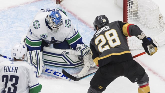 Vancouver Canucks goalie Thatcher Demko makes the save on Vegas Golden Knights' William Carrier during third period Tuesday in a Western Conference playoff game. Demko made 43 saves to win his NHL playoff debut.