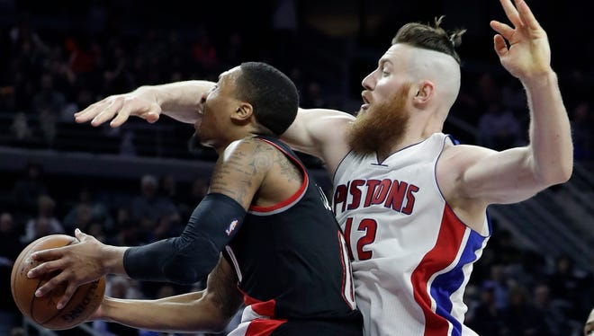 Pistons center Aron Baynes (12) reaches in on Trail Blazers guard Damian Lillard (0) during the second half of the Pistons' 120-113 overtime win Tuesday at the Palace.