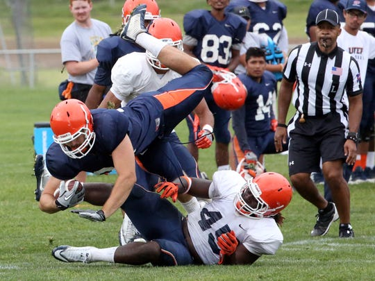 UTEP tight end Sterling Napier, 81, is brought down by linebacker Jamar Smith, 45, in August 2017 at Camp Ruidoso.
