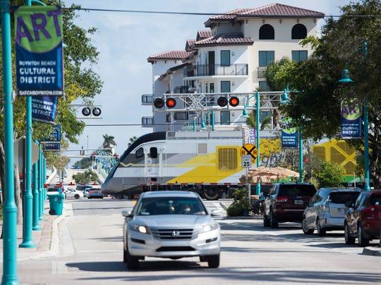 A Brightline train traveling north crosses East Ocean Avenue and Northeast Fourth Street in Boynton Beach.