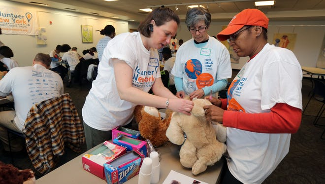 Jennifer R. Machuca, with Volunteer New York, shows Angela Usobiaga from Pleasantville and Tambria Terry from Mount Vernon, how to stuff a therapy bear at the Greenburgh Library in Elmsford, as part of the Volunteer New York Martin Luther King Jr. National Day of Service, Jan. 14, 2017.