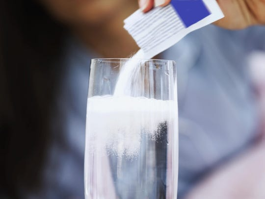 powdered medicine being added to a glass of water