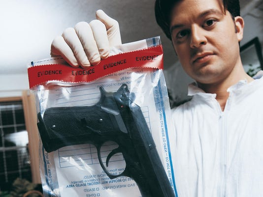 Portrait of a Forensic Scientist at a Crime Scene Holding an Evidence Bag With a Gun Inside