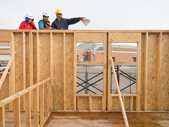 Instructor Nathan Savig talks with Poudre High School students Isaac Cline and Anna Campbell before they begin laying out measurements for trusses on the Habitat for Humanity home they were building in this Nov. 20, 2015, file photo.