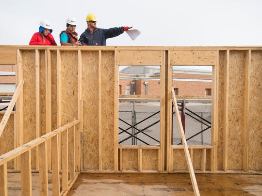 Instructor Nathan Savig talks with Poudre High School students Isaac Cline and Anna Campbell before they begin laying out measurements for trusses on the home they are building in class Friday, November 20, 2015. Students enrolled in the Geometry in Construction course are building a home for Habitat for Humanity.