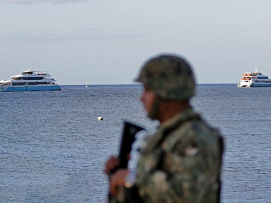 A member of the Mexican Army stands guard near a ferry,