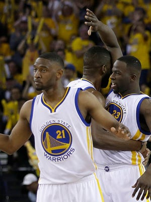 Golden State Warriors guard Ian Clark, from left, center Festus Ezeli and forward Draymond Green react after scoring against the Portland Trail Blazers during the second half in Game 2 of a second-round NBA basketball playoff series in Oakland, Calif., Tuesday, May 3, 2016.
