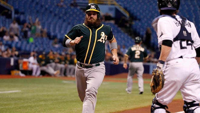 Oakland Athletics catcher Derek Norris scores a run during the second inning against the Tampa Bay Rays at Tropicana Field.
