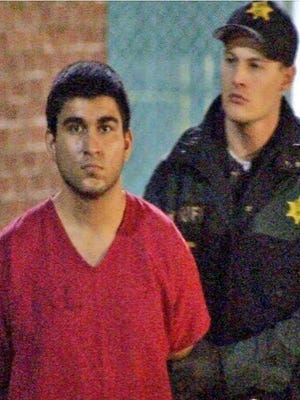 This late Saturday, Sept. 24, 2016, image from video by KIRO7 photographer Jeff Ritter shows suspected Cascade Mall shooter Arcan Cetin at Skagit County Jail in Mount Vernon, Wash., after his arrest in Oak Harbor, Wash., earlier in the evening. Investigators on Sunday tried to piece together information on the 20-year-old suspect in the deadly Washington state mall shootings who was apprehended after a nearly 24-hour manhunt.