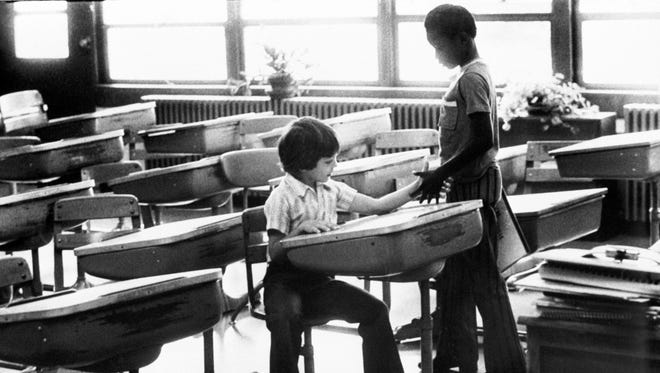 At Greenwood Elementary, Mark Stewart, 8, seated, exchanged introductions with a new classmate, Darrel Hughes, also 8. The photo of the two young men shaking hands became the iconic image from Louisville's days of forced busing to integrate teh city's public school system. By Michael Coers, The Courier-Journal. Sept. 3, 1975