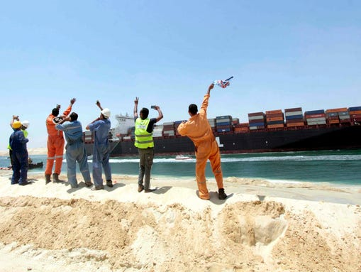 Egytpian workers wave in direction of a container ship sailing